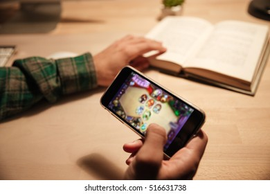 Closeup of man reading book and playing videogames on cell phone at home
