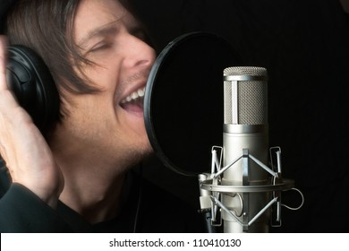 Close-up of a man recording vocals in a sound studio.