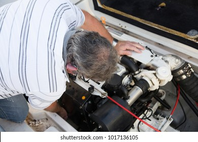 close-up of a man repairing a boat engine under sunny day
