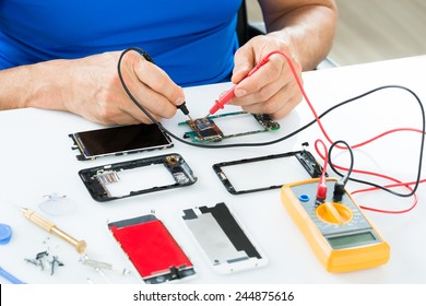 Close-up Of Man Repairing Cellphone With Multimeter