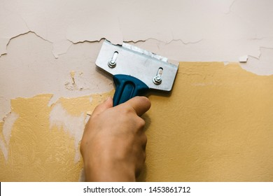 Close-up. A man with a scraper removes the old covering from the wall for further repairs. Wall repair inside the room.