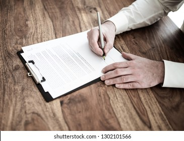 close-up of man signing contract or document at wooden desk