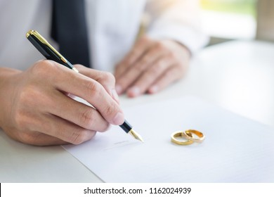 Closeup of a man Signing Contract or premarital agreement, filling petition form agreement of divorce in office at lawyer desk in court room  Conceptual of marriage.