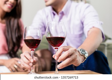 Close-up of man sitting with her girlfriend placing wineglasses on table