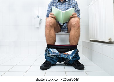 Close-up Of A Man Sitting On Commode Reading Book