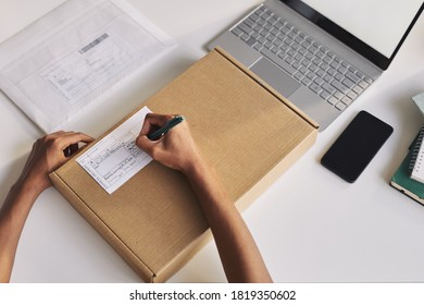 Close-up of man sitting at the table in front of the laptop and filling the form on the parcel he writing his address
