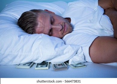 Close-up Of A Man Sleeping With Currency Notes Kept Under His Pillow On Bed