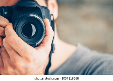 Close-up of a man with a SLR camera in his hands shoots directly into the frame, selective focus on a photo-lens