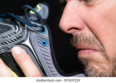 Close-up of a man smelling his running shoe.