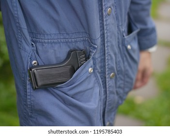 Closeup of a man standing with a firearm in pocket