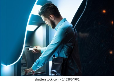 Closeup of a man standing next to ATM machine, night time