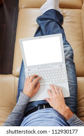 Closeup of Man stretched out on sofa using a modern laptop - Clipping path for laptop screen