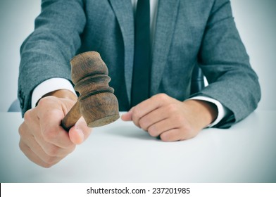 closeup of a man in suit about to struck a gavel