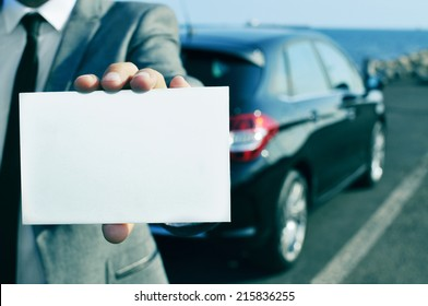 closeup of a man in suit holding a blank signboard with a car in the background