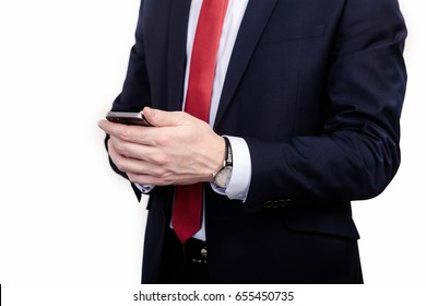 Close-up of a man in a suit holds a mobile phone, on his left hand a watch, on a white background