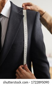 Close-up of man in suit standing in the workshop while designer measuring the breast length