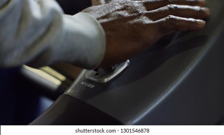 Close-up of man switches speed lever. Man's hand several times presses lever of switching of speeds in car