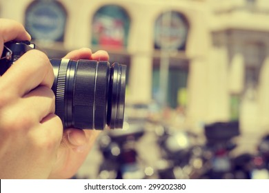 closeup of a man taking a picture with his camera in the street, with a filter effect