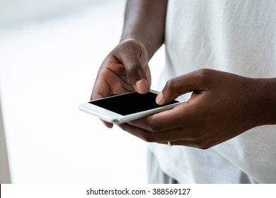 Close-up of man text messaging on mobile phone at home