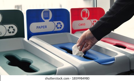 Close-up of man throwing garbage into sorting bins. Media. Man throws garbage into colored bins for sorting. Sorting garbage helps in recycling and supports ecology of nature