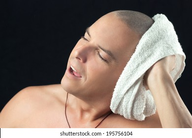 Close-up of a man towel drying his newly shaved head.