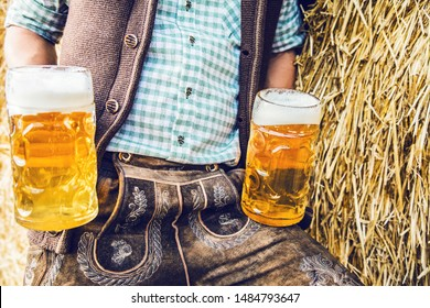 Close-up of man in traditional bavarian Lederhosen with mugs of beer