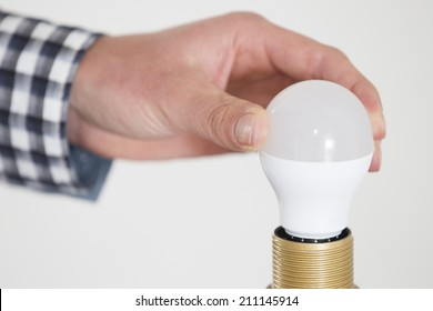 Close-up from a man turning a unlighted lightbulb