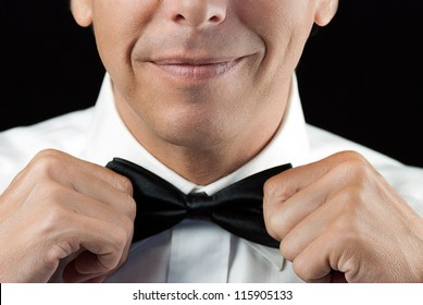 Close-up of a man in a tux straightening his bowtie, two hands, no jacket.