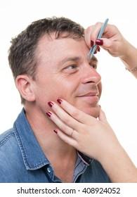 Closeup of man with tweezers plucking eyebrows