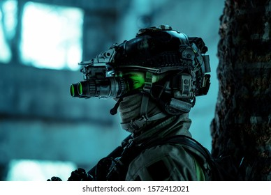 Closeup man uniform with machine gun and turned on night vision device. Airsoft soldier with green light on face in night building. Side view