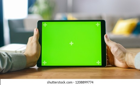 Close-up of Man Using Green Mock-up Screen Digital Tablet Computer in Landscape Mode while Sitting at His Desk. In the Background Cozy Living Room.