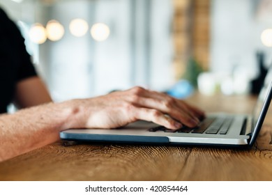 Closeup of man using laptop in a cafe. Freelance background  concept.