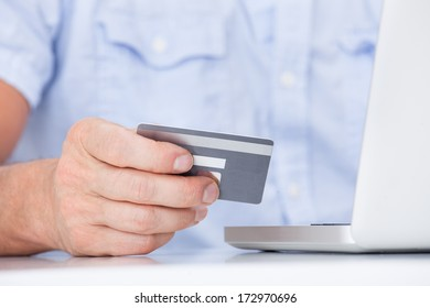 Close-up Of A Man Using Laptop And Credit Card