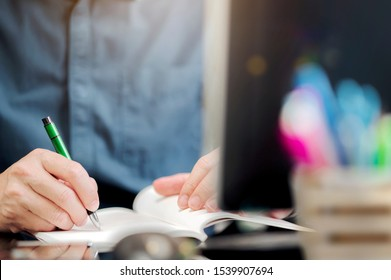 Nahaufnahme mit Stift, der auf Notebook schreibt, während er im modernen Büro sitzt.