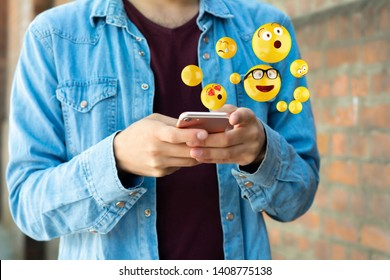 Close-up of man using smartphone sending emojis. Social concept.