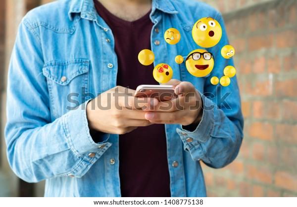Close-up of man using smartphone sending emojis. Social concept.