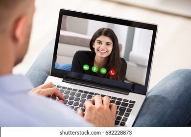 Close-up Of A Man Video Conferencing With Her Happy Wife On Laptop