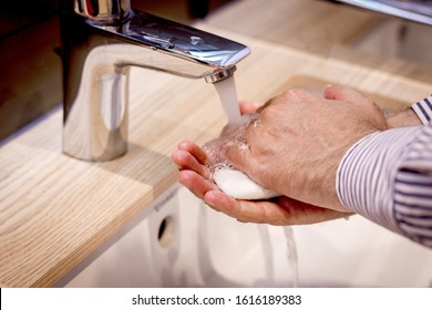 Close-up of man washing hands with soap under bathroom sink.