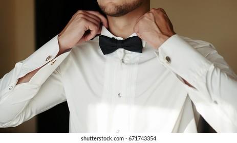 Close-up of man wearing Black Tie straightens his bowtie.