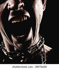 Closeup of a man wearing a chain around his neck with his mouth wide open in a dramatic scream. High contrast on black background