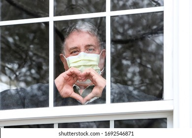 Closeup of a man wearing a face mask making heart symbol with hands at the window