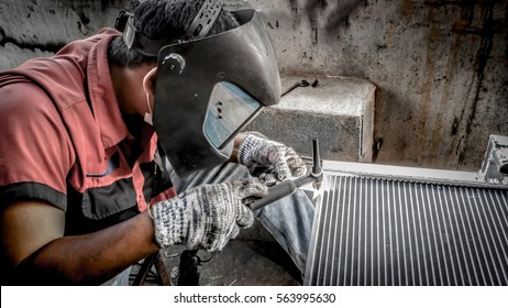 Closeup of man wearing mask Welding steel structures and bright sparks  in a workshop