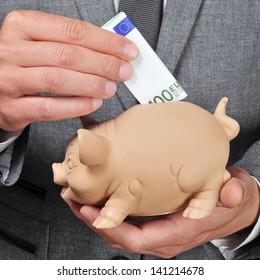 closeup of a man wearing a suit introducing a euro bill in a piggy bank