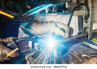 A close-up man is weld metal with a welding machine, blue sparks fly to the sides, the top view