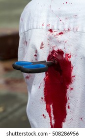 Closeup of a man if white shirt stabbed by a scissor...