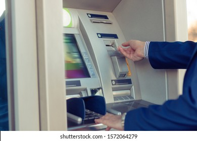 Close-up of man withdrawing money at ATM cash machine.