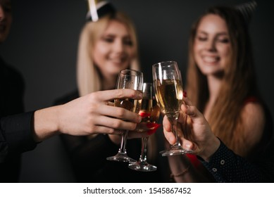 Close-up of man and woman clinking with champagne glasses. Four beautiful and cheerful friends in festive clothes on background.