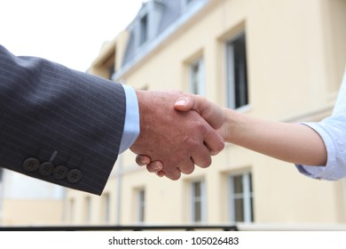 Close-up of man and woman shaking-hands outdoors