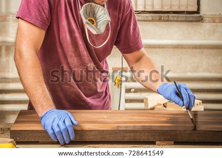 Close-up A man in a work shirt paints a wooden  with a wooden brush for protection against corrosion in the garage