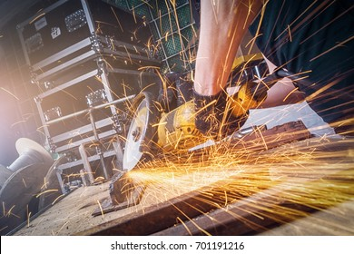 Close-up of a man  worker cutting metal with a hand-held circular saw with a yellow handle in the workshop, in the background a lot of generalization, yellow spark-sparks fly in different directions